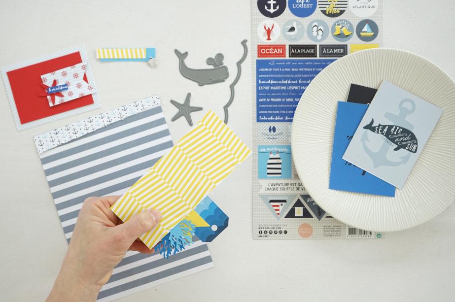 2. Pour une seconde page, couper un fond de page dans le papier Cézembre. Faire un rectangle de 15,2 x 6,5 cm dans un autre papier imprimé. Astuce : Glisser dessous avant de le coller sur le fond de page des petits éléments de décoration : comme un tag, un fanion, et des petits motifs découpés avec les dies de différentes couleurs.  Pour une dernière touche de matière et volume : faire une couture décorative sur le bord de ce papier. Coller le ensuite sur votre fond de page à 9 cm du haut. Ajouter un rectangle de papier rouge de 6,5 x 8,5 cm collé au préalable sur une étiquette du papier Ouessant et y coller qui une photo. Compléter par des embellissements : stickers, découpes avec les dies etc…