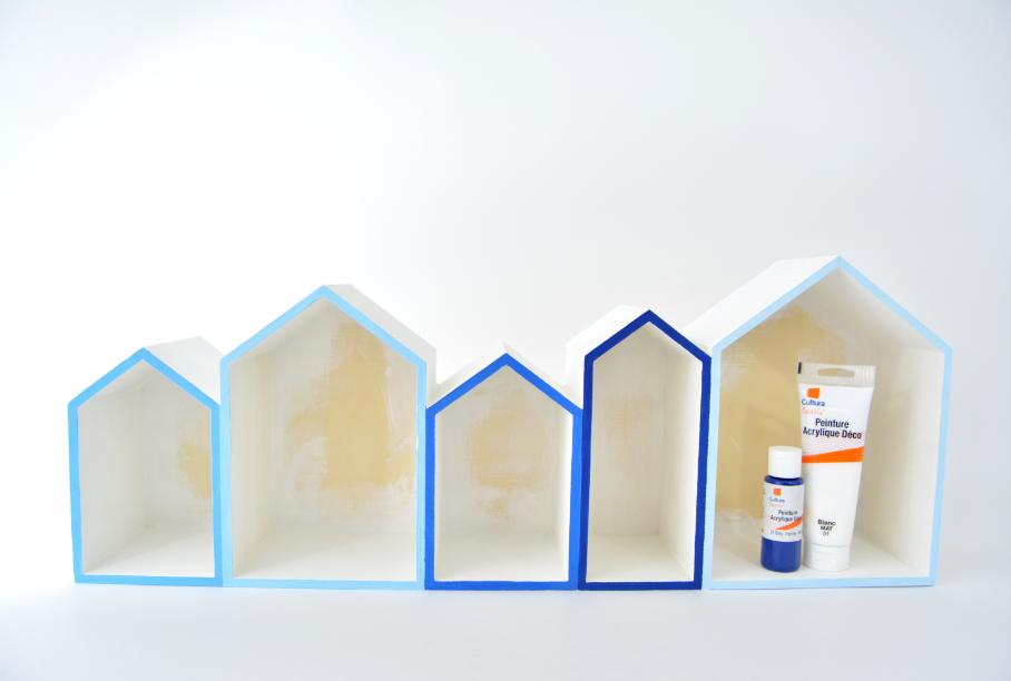 1. Passer une sous-couche de gesso sur l'ensemble du support à l'exception des toits et du fond. Le peindre en blanc. Laisser sécher. Préparer des mélanges de peinture «bleu marine» et «blanc» pour créer des nuances de bleus puis peindre les tranches sur les façades de chaque maison. Protéger les bords de ruban de masquage.