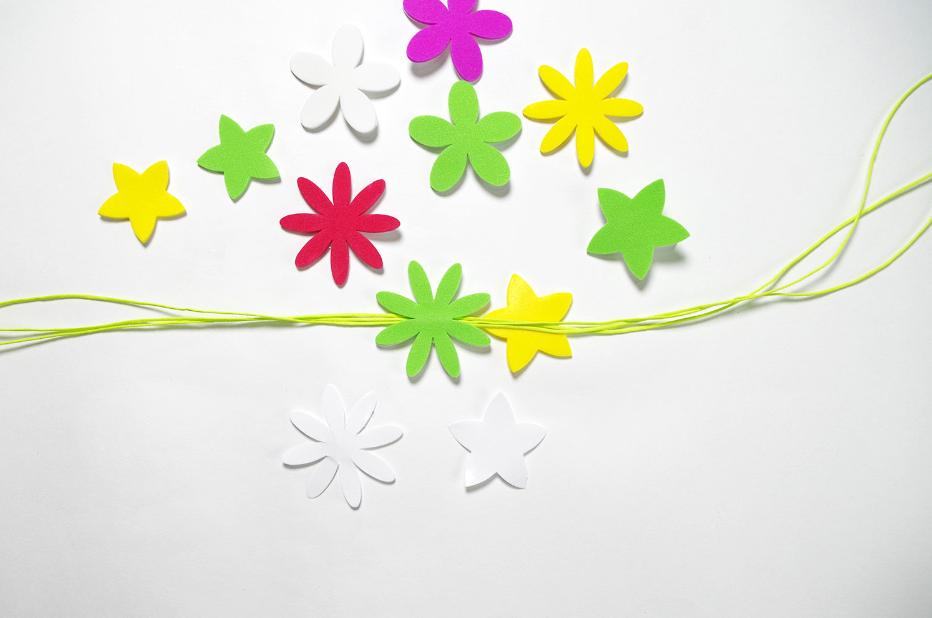 2. Sélectionner des fleurs vertes qui seront la base «feuillage» de la couronne et autant de formes jumelles. Placer le milieu des trois longueurs de ficelle face à soi. Sélectionner deux fleurs identiques, retirer les pellicules qui protègent le coté collant des fleurs et coller dos à dos en plaçant les trois ficelles vertes entre elles, afin de maintenir les trois longueurs ensembles.