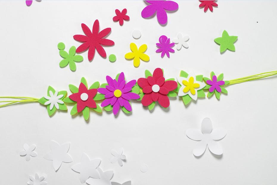 3. Continuer à fleurir la couronne en collant des fleurs par-dessus le feuillage en mixant formes et ronds de couleur. Nouer la couronne de fleurs sur le front de l' enfant.