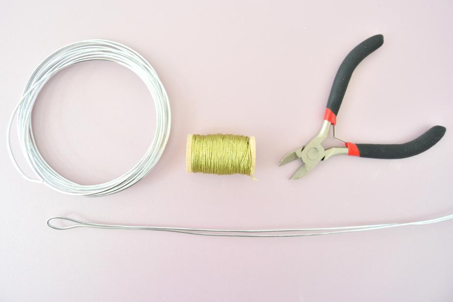 La base de la couronne :  1. Couper une longueur de 60 cm dans le fil d'aluminium à l'aide de la pince à bijoux coupante. Le plier en deux en formant une boucle au niveau du pli. Rabattre les deux extrémités de fils pour former une double boucle de l'autre côté.
