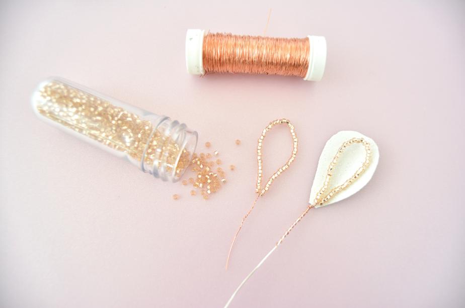 2. Pour créer des feuillages perlés, découper une longueur de fil cuivré et insérer autant de perles de rocailles nécessaires à la longueur souhaitée. Former une boucle et nouer le fil. L'attacher à un feuillage en papier. Répéter cette action pour tous les feuillages.