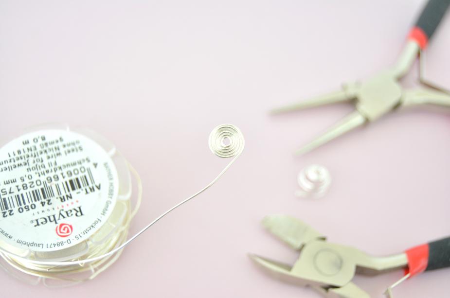 Création des accessoires fleuris à ressort : 1. Enrouler en spirale le fil à bijoux à l'aide de la pince ronde. Couper l'extrémité à l'aide de la pince coupante.