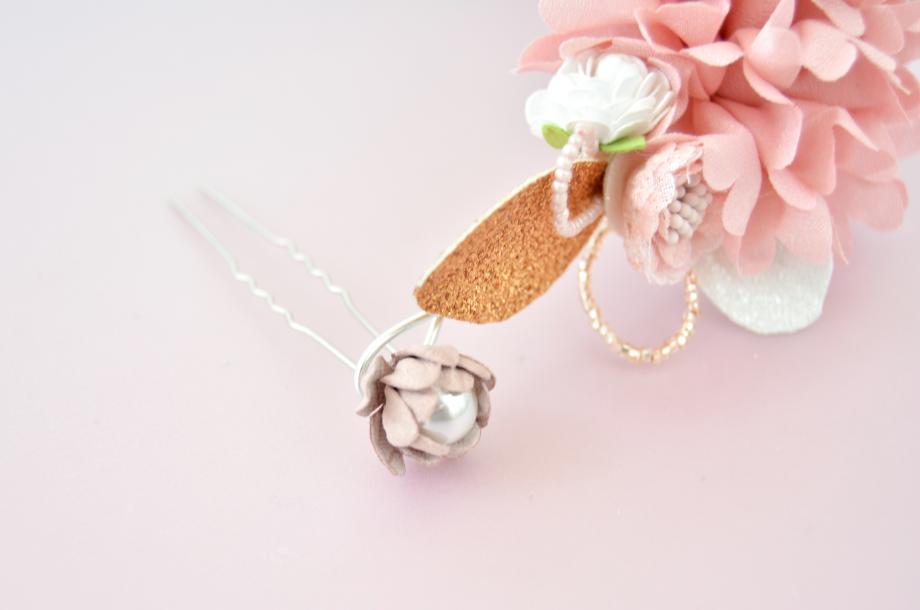 2. Personnaliser les épingles à chignon d'une fleur perlé collée à l'aide de la colle à bijoux. Les insérer dans chaque boucle de la couronne pour la fixer sur le chignon de la Mariée.
