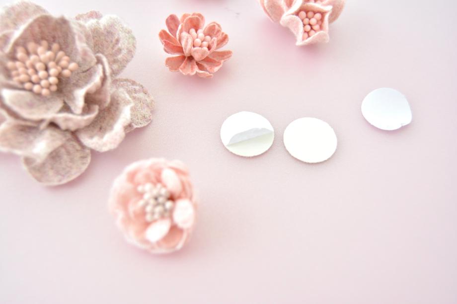 1. Créer pour chaque fleur ne disposant pas de pastilles de feutrine des ronds de papiers pour faciliter le collage sur le ruban : Perforer deux ronds dans les papiers adhésifs pailletés et coller dos à dos les faces adhésives. Répéter cette action pour toutes les fleurs.
