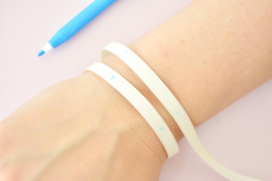 Idée n°1 : Créer un bracelet multi lien avec le ruban 6 mm. Marquer les repères du poignet à l'aide d'un feutre effaçable pour le collage des fleurs dans la bonne zone visible.