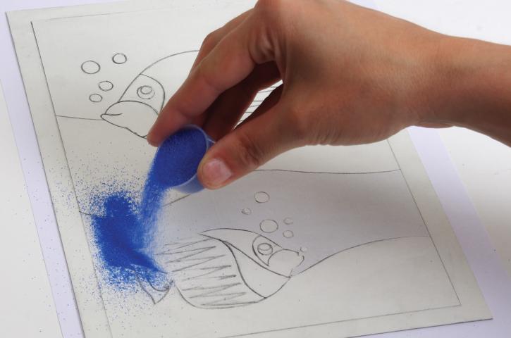 5. Placer une feuille de papier sous le carton et saupoudrer le sable sur les parties collantes et l'étaler avec le doigt. Commencer par les couleurs les plus foncées.