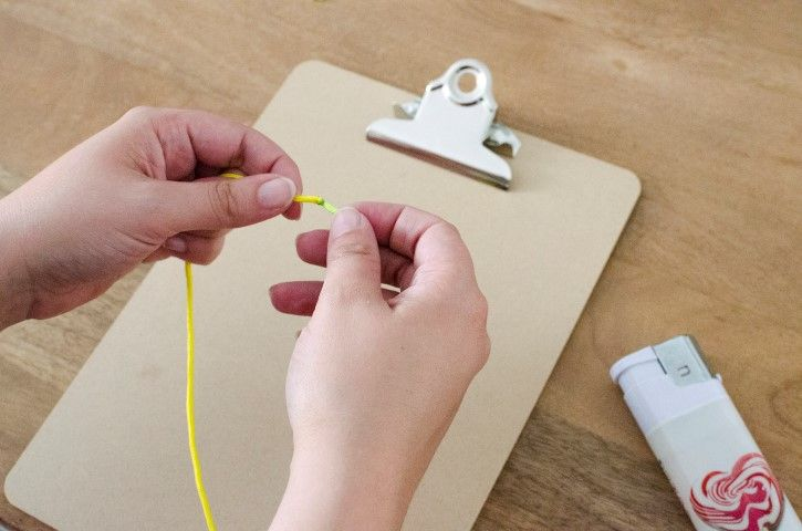 2. Manipulation par un adulte : Brûler les 2 extrémités des cordons choisis pour les coller et n'avoir plus qu'un seul long cordon. Prendre les mesures du poignet. Faire une boucle dans la partie femelle du clip, et accrocher le clip de façon à ce qu'il tienne bien en place pendant le tissage. Passer les cordons dans l'autre partie du clip, la longueur entre les 2 clips doit correspondre à la mesure du poignet.