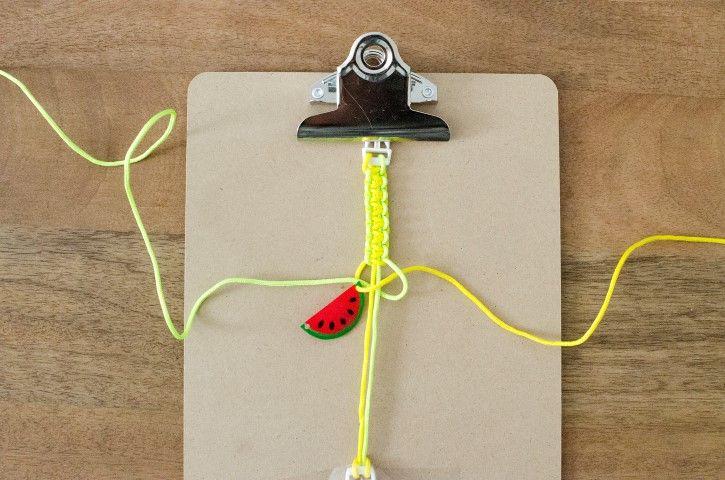 4. Répéter l'opération. A moins de la moitié du bracelet, passer un des cordons dans le 1er trou du pendentif.