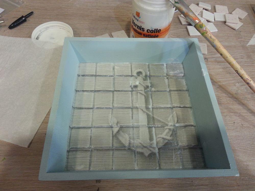 Coller votre serviette à l'aide du vernis colle puis découper avec un scalpel le long des tesselles