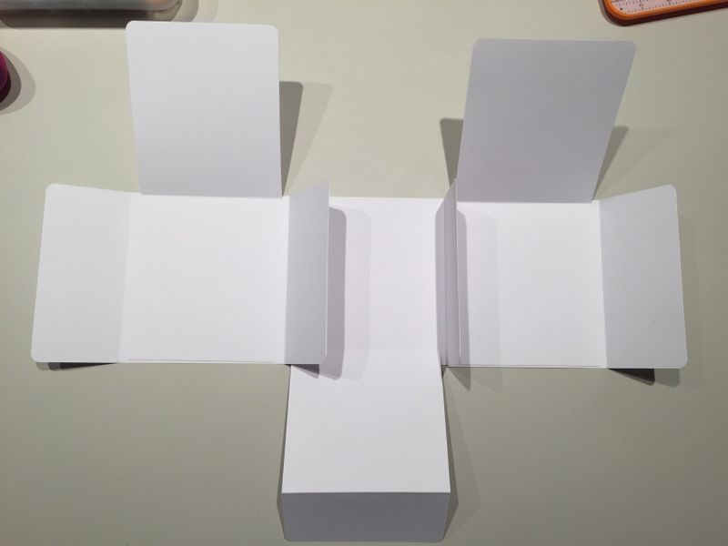7. Coller les 2 feuilles 28 x 12 cm sur les pages de chaque extrémité, la pliure vers le haut. 8. Coller sur la partie du milieu la feuille 30,5 x 18 cm, la  pliure vers le bas pour finaliser la structure.