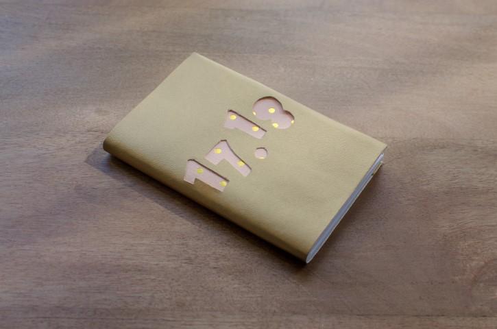 5. Coller le cuir sur l'ensemble de l'agenda, en repliant les centimètres supplémentaires vers l'intérieur.