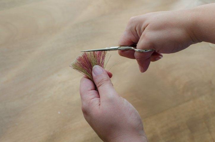 9. Couper le bas du pompon pour obtenir des fils de même longueur.
