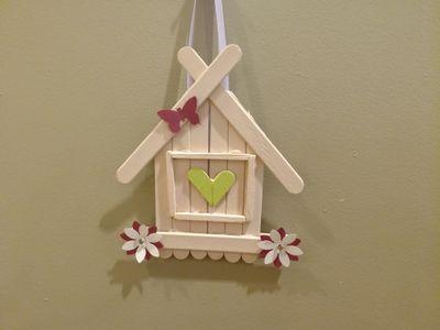 pour cette création j'ai simplement regroupé des bâtonnets et collé au pistolet à colle pour donner une forme de maison , puis j'ai peint à la peinture acrylique et décoré avec quelques fleurs papiers réalisées à l'aide d'une perforatrice, et le tour est joué.