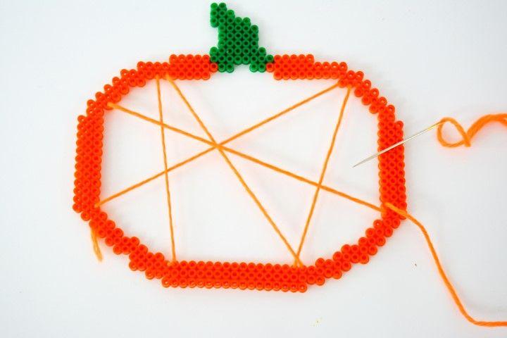 3. Réalise une toile à l'aide d'une aiguille et de la mini pelote de laine orange : passe le fil de laine dans un trou d'une perle à repasser et tisse d'un bout à l'autre la citrouille. Répète plusieurs fois l'action.