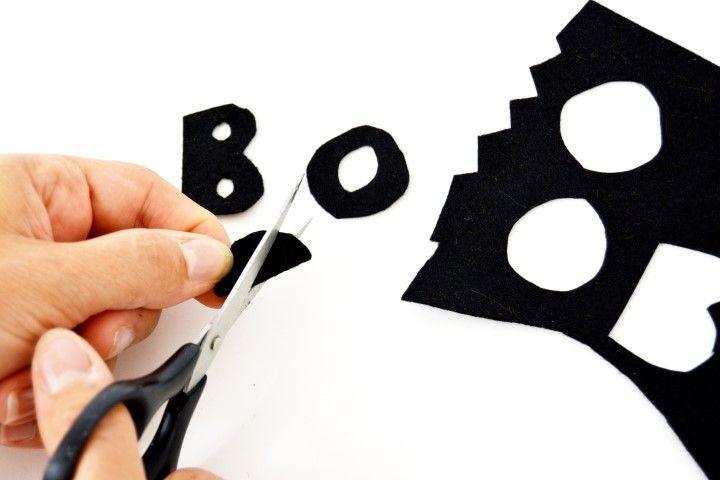 """5. Pour créer le mot """"BOO"""" découpe les lettres dans la feutrine noire. Astuce : pour évider facilement les ronds à l'intérieur des lettres, plie les lettres en deux et coupe un demi-cercle."""