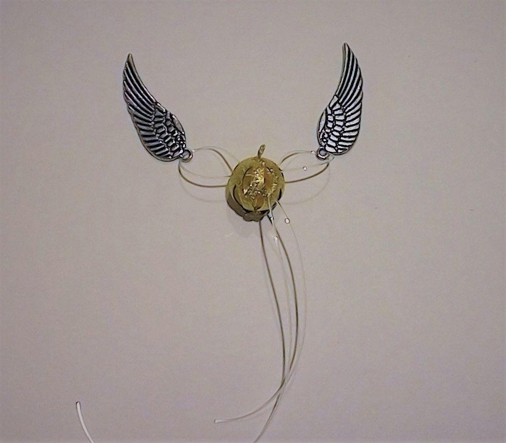 Enfiler les Ailes de chaque côtés de la perle en traversant celle-ci avec le fil nylon et en effectuant un double noeud pour resserrer l'ensemble. Répeter l'opération dans l'autre sens  puis couper les extrémités des fils au maximum à l'intérieur de la perle.