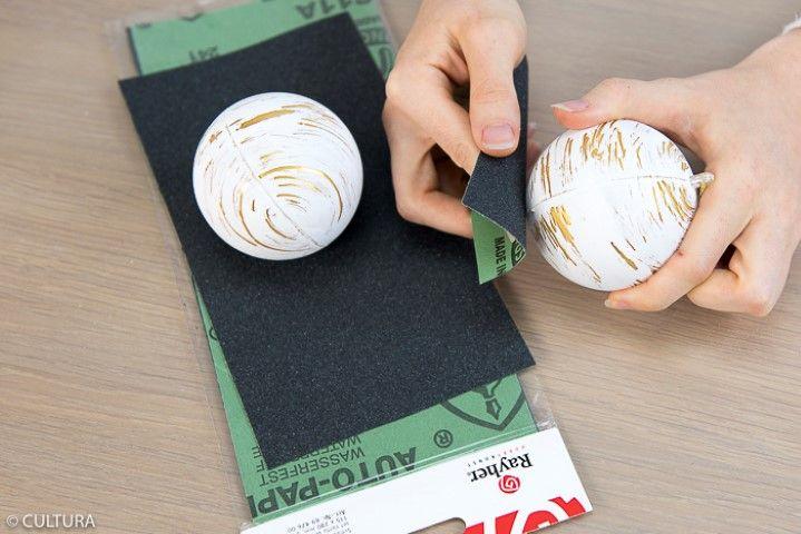 2. Recouvrir l'extérieur de la boule avec la peinture Chalky Finish blanche. Laisser sécher puis poncer horizontalement l'extérieur de la boule, de façon irrégulière, pour faire apparaître le doré et l'effet « écorce de bouleau ».