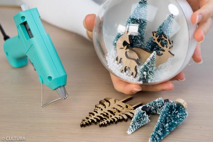 Coller les accessoires décoratifs en bois et les mini sapins sur la partie basse de la boule à l'aide d'un pistolet à colle. Verser les billes polystyrène dans une moitié de boule puis fermer la boule.