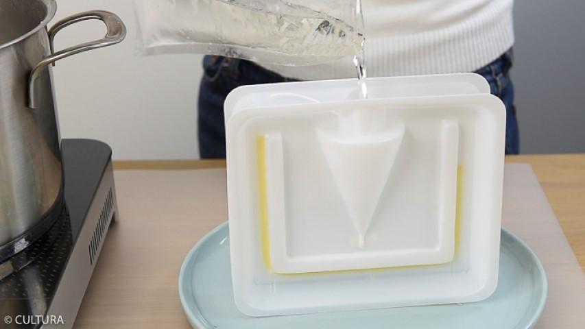 2. Assembler le moule en respectant les instructions d'utilisation du produit. Placer la mèche et la stabiliser au centre. Le poser verticalement. Verser 2 cm de cire. Réfrigérer. Remplir jusqu'en haut du moule avec la cire liquide banche. Réserver au réfrigérateur