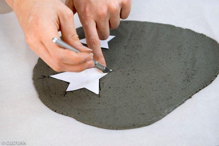 3. Télécharger, imprimer et découper le gabarit des étoiles. Poser les gabarits sur le béton créatif et couper les étoiles à l'aide d'un cutter de précision. Créer un trou à l'aide d'un cure-dent pour la suspension. Laisser sécher 24h.