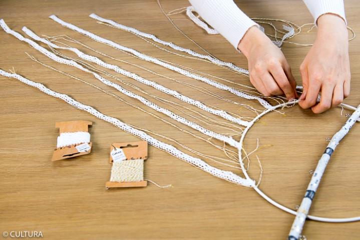 2. Suspendre une trentaine de ficelles (30 à 60 cm) et quelques rubans dentelle à la branche et à l'anneau. Astuce : pour affiner la largeur des rubans de dentelle, les couper en deux dans leur longueur.