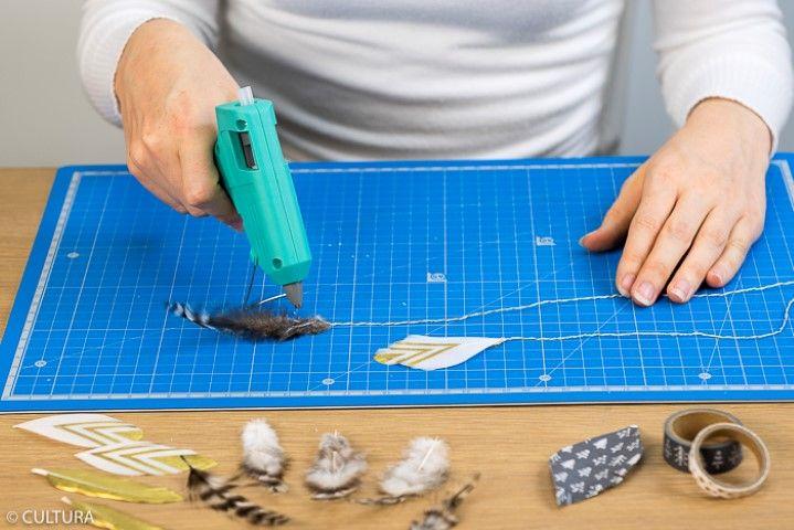 4. Coller les plumes aux ficelles. Idées + : Pour créer des plumes en papier, positionner au recto et au verso d'un papier blanc des bandes de masking tapes. Découper des formes de plumes à l'aide du gabarit. Entailler la partie haute des plumes pour les suspendre aux ficelles.