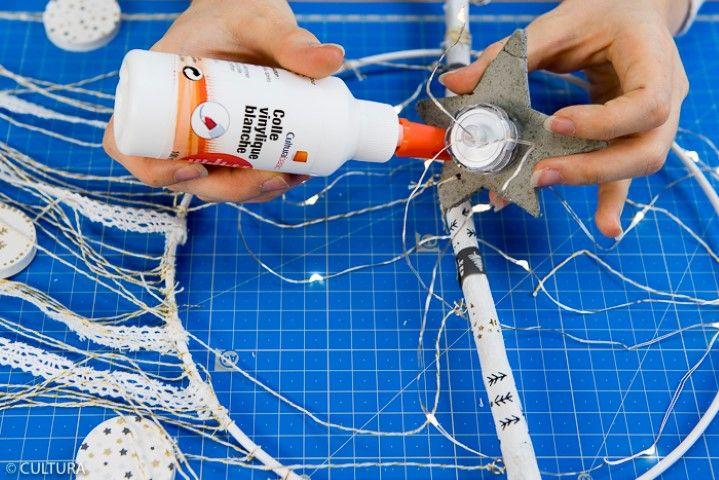 5. Répartir et fixer harmonieusement sur les ficelles restantes les étoiles en béton, les perles et les accessoires décoratifs. Astuce : Utiliser une aiguille pour enfiler facilement la ficelle dans les perles. Coller une étoile en béton sur le boitier de commande de la guirlande led à l'aide de la colle blanche. Laisser sécher. Fixer la guirlande led avec la ficelle en haut de l'anneau et positionner l'étoile en béton au centre de la branche.