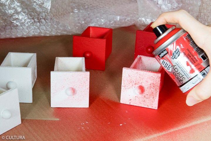 Peinture des tiroirs et des accessoires : Appliquer une sous-couche de gesso sur l'ensemble des tiroirs et des accessoires décoratifs. Peindre onze tiroirs et les accessoires décoratifs avec la peinture Déco crème blanche. Laisser sécher. Bomber les tiroirs restants avec le Déco spray rouge. Laisser sécher.