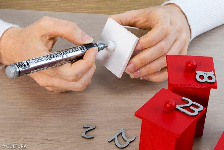 Peindre les numéros de l'avent correspondants aux tiroirs rouges et les boutons des tiroirs blancs avec le Déco marker argenté. Bomber en rouge les numéros restants. Coller les numéros de l'avent sur les tiroirs.