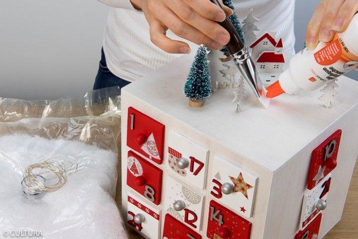 Enduire de colle la scénette et la boule polystyrène puis saupoudrer l'ensemble de neige artificielle. Laisser sécher puis disposer une guirlande micro led pour finaliser la décoration du calendrier.