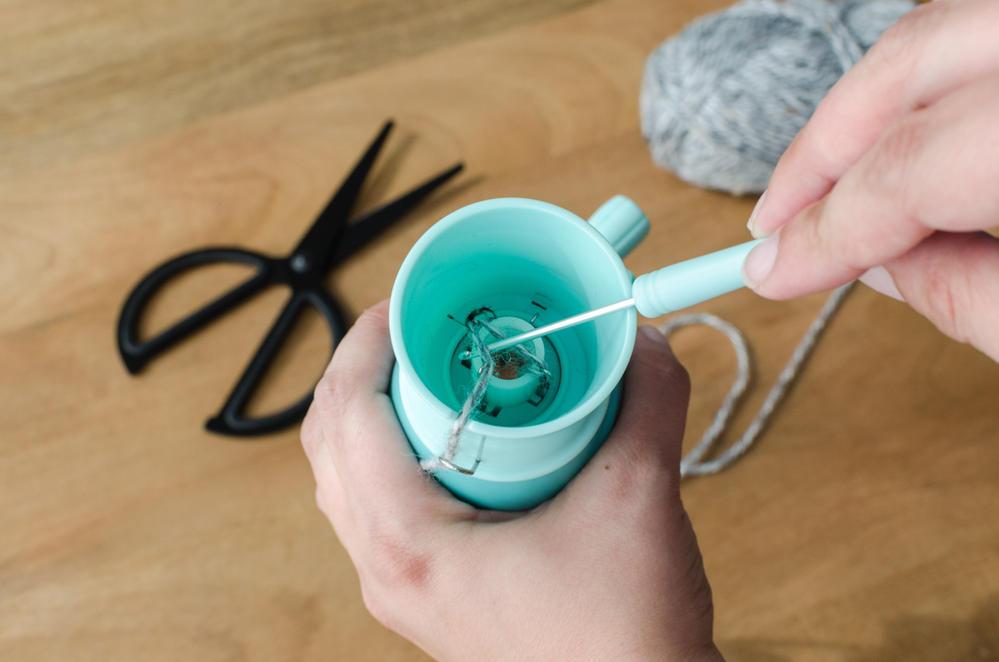 1. Enfilez votre fil de laine dans le tricotin en suivant les indications du fabricant pour commencer : bloquer le bout avec le poids, le 1er et le 3ème crochet doivent attraper la laine, mais pas le 2nd et le 4ème.