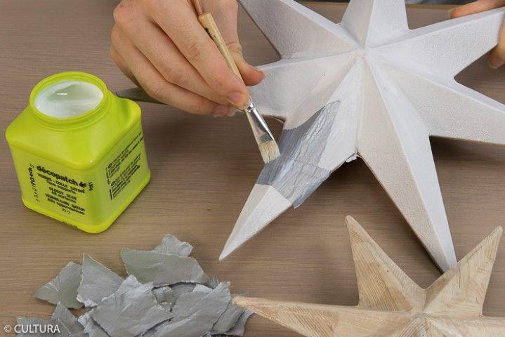 3. Recouvrir une étoile des morceaux de papiers déchirés. Lisser le papier à l'aide du pinceau enduit de vernis colle. Répéter l'action pour la seconde étoile. Laisser sécher.