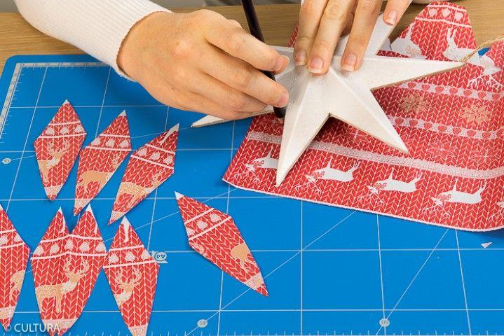 L'étoile rouge : 1. Reporter les dimensions d'une branche de l'étoile au dos du papier rouge dans le sens du motif imprimé effet « tricot ». Découper et répéter cette action pour chaque branche.