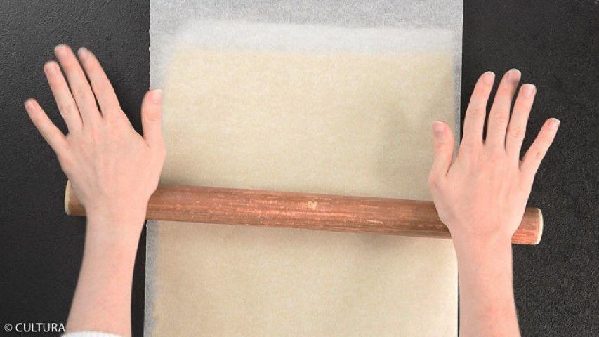 2. Abaisser* la pâte sur une épaisseur de 5 mm entre deux feuilles de papier sulfurisé. Réserver au frais une bonne heure.