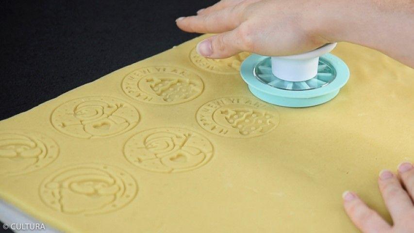 3. Assembler le tampon et tamponner la pâte. Retirer le « disque empreinte » du support et presser l'emporte-pièce rond transparent en exerçant un mouvement circulaire. Retirer la pâte autour du biscuit.