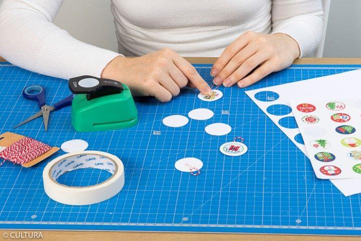 4. Pour créer des étiquettes à suspendre, perforer des ronds dans un papier blanc puis coller les stickers de l'avent. Couper une petite longueur de ficelle bicolore pour créer la suspension et la maintenir au dos des ronds avec un morceau de ruban de masquage.