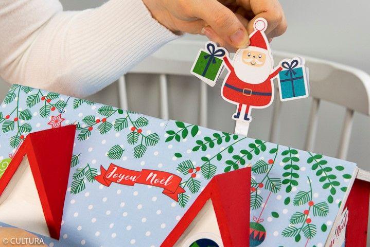 7. Découper une languette d'environ 3 cm dans le papier blanc, marquer un pli d'1 cm. Coller dos à dos deux formes de découpes Père-Noël en insérant au préalable le pli de la languette aux pieds du Père- Noël. Soulever le toit, glisser et coller la languette pour maintenir le Père-Noël à la verticale sur le toit.