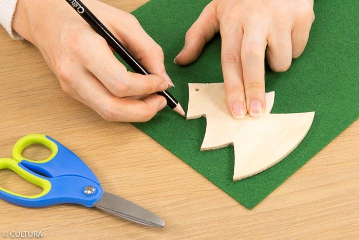 Décoration des formes en bois : • Idée n° 1 : Le sapin Ôter la ficelle du support. Reporter deux fois la forme bois « sapin » sur la feuille de feutrine verte. Couper