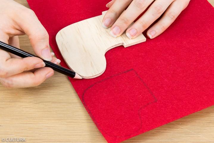 Idée n° 3 : La chaussette Ôter la ficelle du support. Reporter deux fois la forme bois « chaussette » sur la feuille de feutrine rouge, en évitant la partie haute. Couper et coller sur le support.