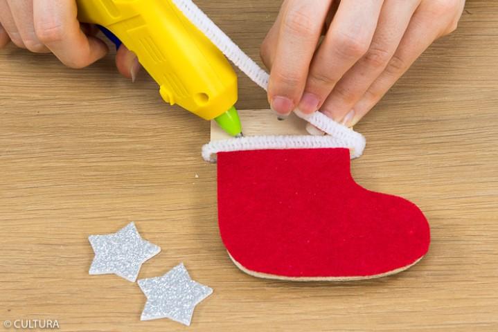 Entourer la partie haute de la chaussette avec des fils chenille et les coller. Finaliser la décoration en collant un sticker adhésif « étoile ».