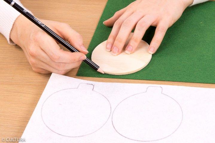 • Idée n° 2 : La boule de Noël Ôter la ficelle du support. Reporter deux fois la forme bois « boule » sur la feuille de feutrine blanc pailleté et deux fois la partie basse de la boule sur la feuille de feutrine verte. Couper.