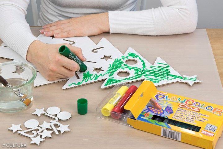 1. Retirer les motifs perforés du sapin. Peindre les deux parties du sapin à l'aide du stick gouache vert : Etaler le stick sur le sapin en carton puis diluer la gouache à l'aide d'un pinceau humide.
