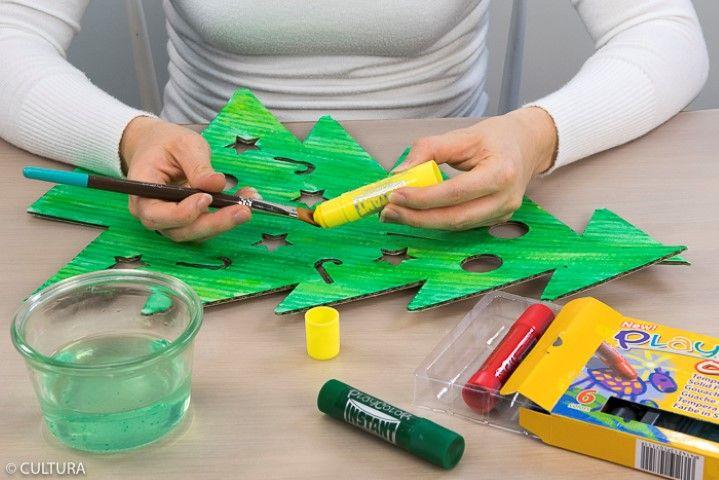 2. Enduire le pinceau humide du stick gouache jaune et l'appliquer par petites touches sur le sapin pour créer des nuances de verts.