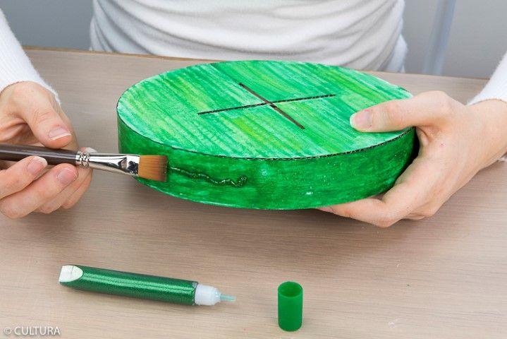 3. Répéter l'action pour colorer la base ronde du sapin. Conseil : deux couches du stick gouache vert sont nécessaires sur le contour de la base. Laisser sécher. Pour un rendu scintillant, appliquer la colle pailletée verte sur la base ronde et l'étaler au pinceau. Laisser sécher.