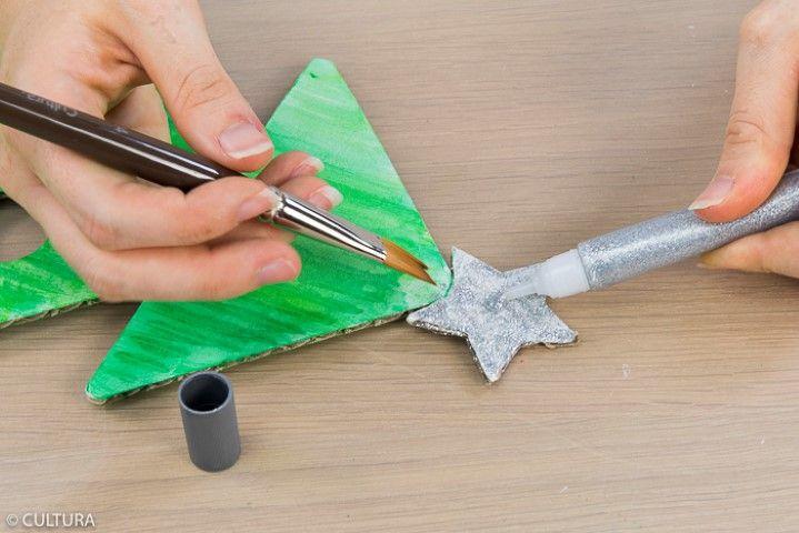 6. Appliquer la colle pailletée argentée sur l'étoile au sommet du sapin. Laisser sécher.