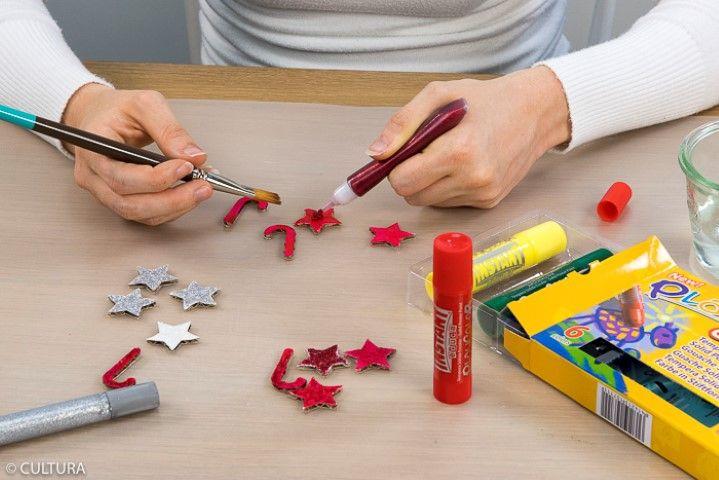 5. Peindre les motifs perforés « étoile » et « canne à sucre » à l'aide des sticks gouache puis les recouvrir de colle pailletée. Laisser sécher.