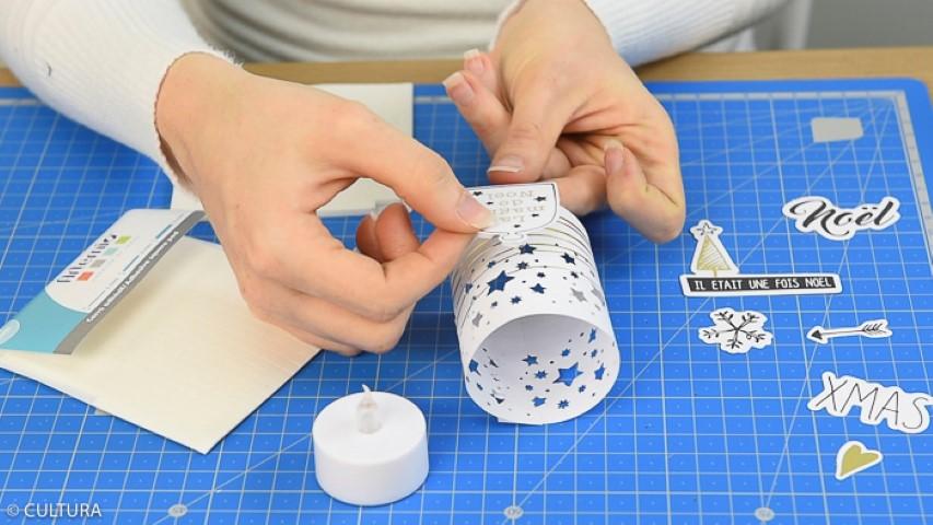 3. Découper une bande à 15 x 5 cm et la placer autour d'une bougie led pour créer un mini photophore. Coller les extrémités. Personnaliser d'une forme de découpe de la collection. Idée : Utiliser les carrés de mousse adhésifs pour donner du relief à la forme de découpe.