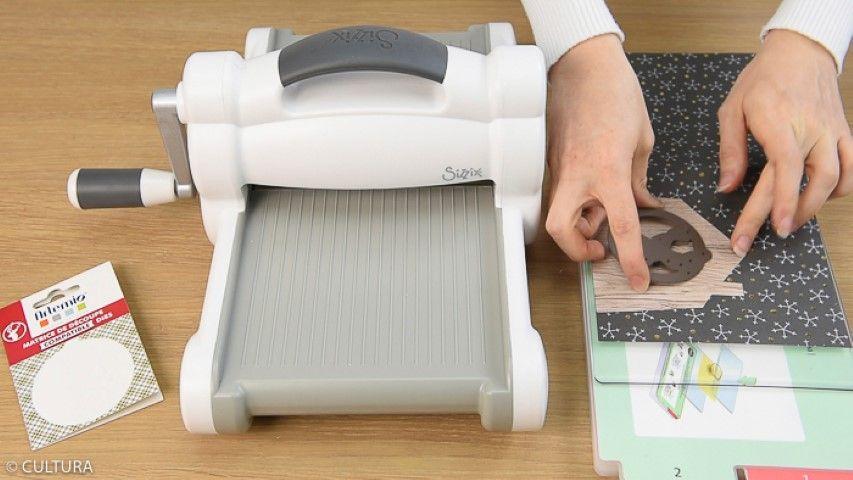 Idée n°2 : Carte de Noël Pour obtenir une carte double 15 x 15 cm, plier en deux un papier 15 x 30 cm de la collection. Télécharger, imprimer, reporter et découper le gabarit « maison » au dos d'un papier effet bois et le coller sur la couverture de la carte. Pour créer un motif ajouré sur la carte, utiliser une machine de découpe : Déplier la carte à plat et la poser sur une plaque fournie avec la machine. Placer la matrice de découpe « médaillon » au centre de la maison et découper le motif en suivant les recommandations d'utilisation de la machine.