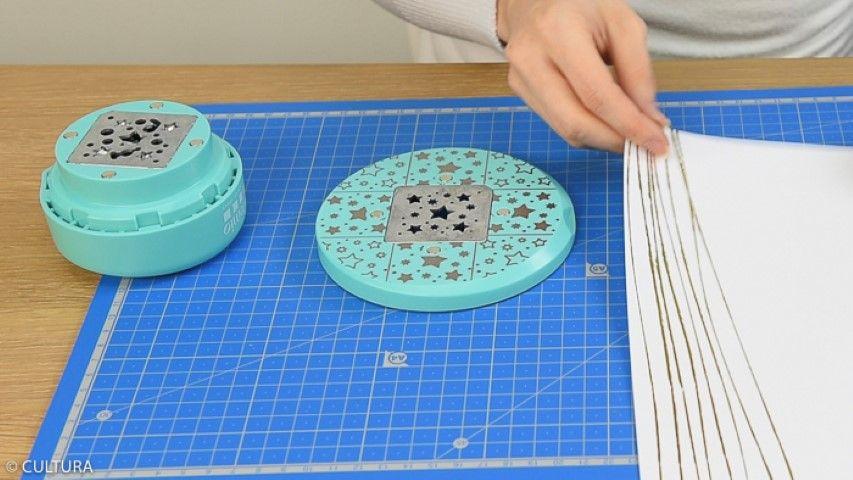 Idée n°1 : Création d'un photophore 1. Placer le papier blanc et doré du bloc sur la base de la perforatrice. Positionner le sommet de la perforatrice, il s'aimante automatiquement.
